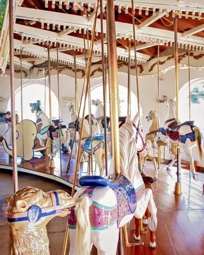 carousel horses photo white with purple saddles waiting for riders