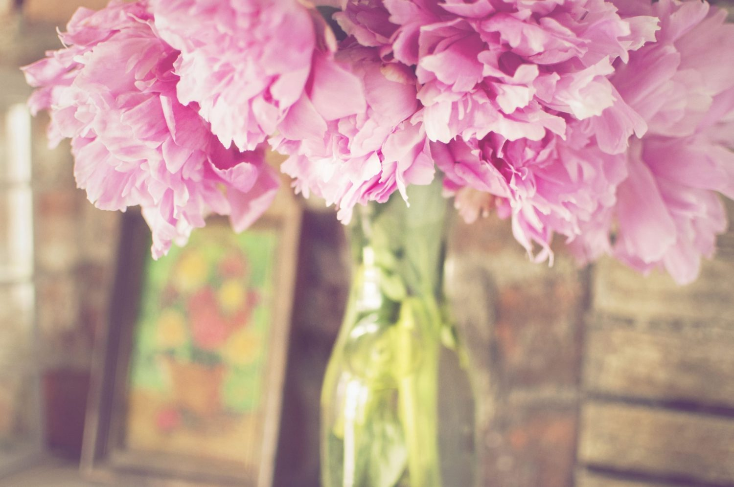 pink peonies in clear milk glass vase by brick wall
